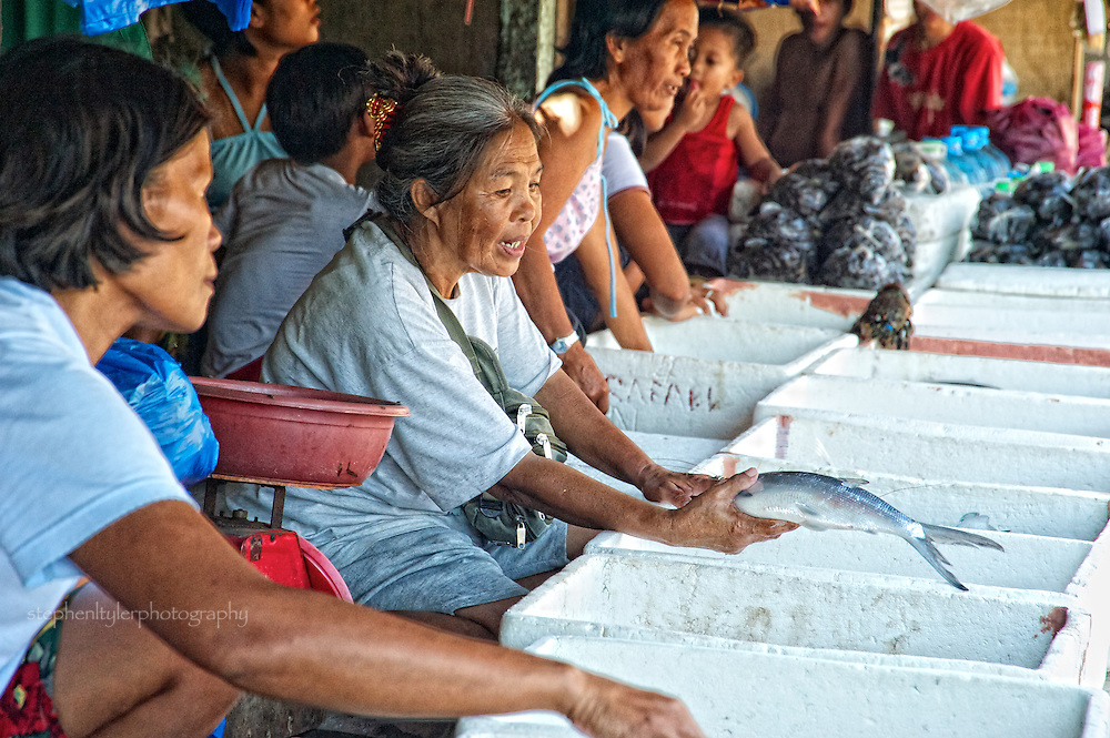 Fish vendors at wet market in Real, a rural town located on the Pacific coast of the Philippines in Quezon Province, attempt to persuade a customer.