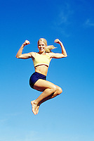 A young woman jumping and flexing her muscles in mid air.