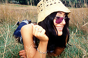 A girl laying in long grass, smiling, wearing a hat and sunglasses, UK 2004