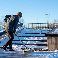 Braving the cold Wednesday evening, RJ Birch, 20 starts to clear the snow at the new skate park in Gallup.