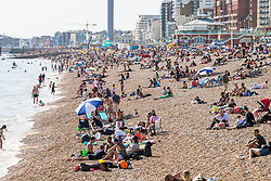 © Licensed to London News Pictures. 12/07/2020. Brighton, UK. Members of the public take to the beach in Brighton And Hove on Sunday afternoon as sunny and warm weather is hitting the seaside resort. Photo credit: Hugo Michiels/LNP