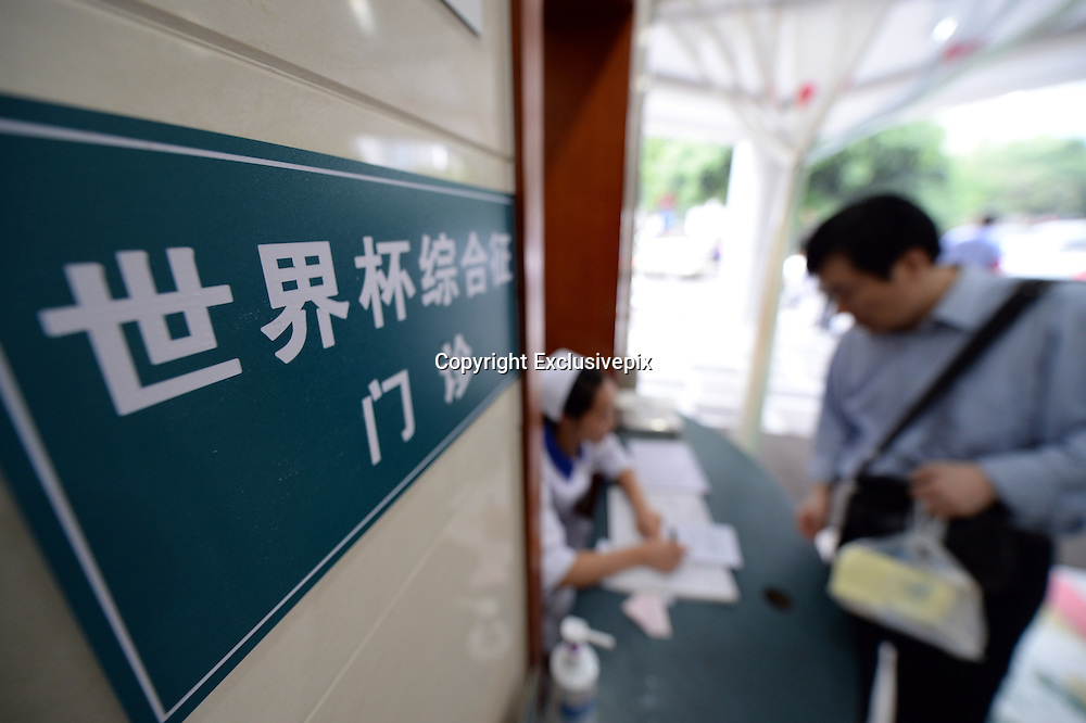 CHENGDU, CHINA - JUNE 24: (CHINA OUT) <br /> <br /> &quot;World Cup Syndrome Clinic&quot; In Chengdu Hospital Reminds Citizens To Avoid Sleep Deprivation<br /> <br />  A medical staff member explains the treatment process of the &quot;World Cup Syndrome Clinic&quot; of No. 3 People's Hospital to soccer fans on June 24, 2014 in Chengdu, Sichuan Province of China. Over a week after the 2014 World Cup began, the No. 3 Peoples Hospital in Chengdu opened a &quot;World Cup Syndrome Clinic&quot;, specifically for soccer fans that developed health issues from staying up late to watch the World Cup. A spokesperson of the hospital says that everyday since the World Cup began, there have been patients coming in for counselling or treatment on sleep deprivation caused by staying up all night to watch the World Cup. There have also been cases when fans overeat while watching the World Cup, causing burden in the gastrointestinal tract. The spokesperson says that sleep deprivation can cause mood depression and anxiety, decreased immune function, and can easily lead to neurasthenia or flu symptoms.<br /> &copy;Exclusivepix