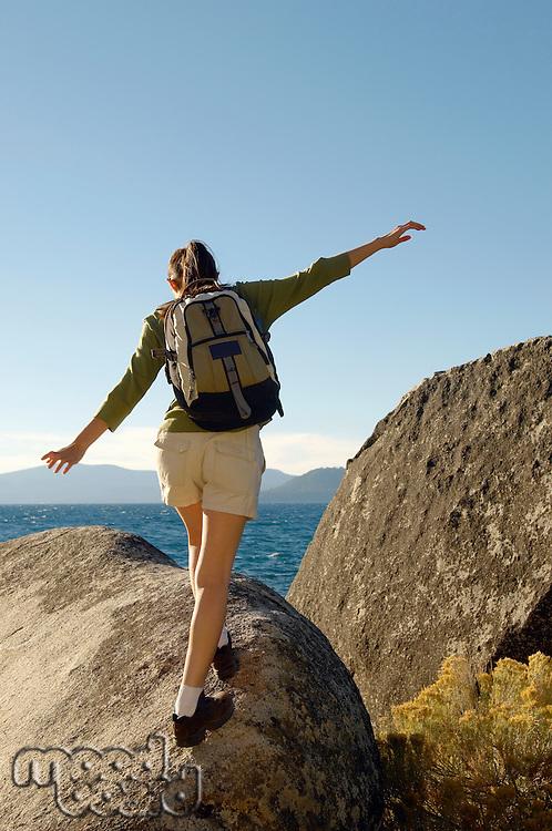 Hiker balancing on boulder at coast
