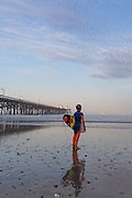 Young Boy Standing on Beach with Surfboard