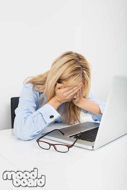Stressed businesswoman with laptop at office desk