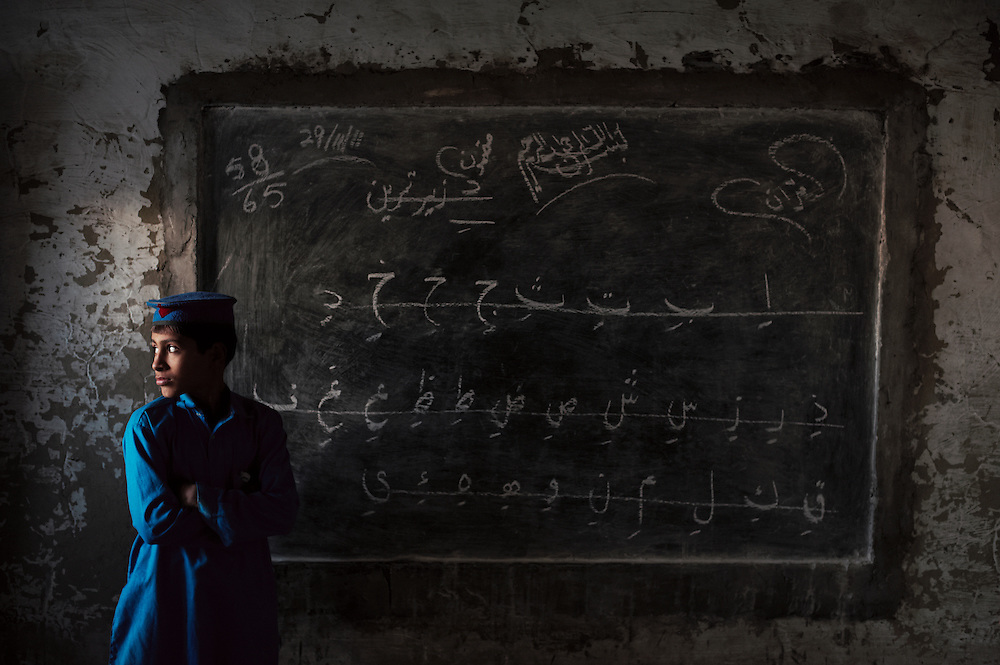 Pakistan/ Afghan refugees/ A student stands next to a blackboard at a school in the Khazana refugee camp, Peshawar. The camp was established when refugees flooded across the border from Afghanistan during the 1979 Soviet occupation. The refugee camp has a population of 2500 and during the 2010 floods that swept through Pakistan most families were affected. The majority of people rebuilt their houses after the floods with their own resources. The most vulnerable also received support from UNHCR for reconstruction. UNHCR/Sam Phelps/ November 2011.