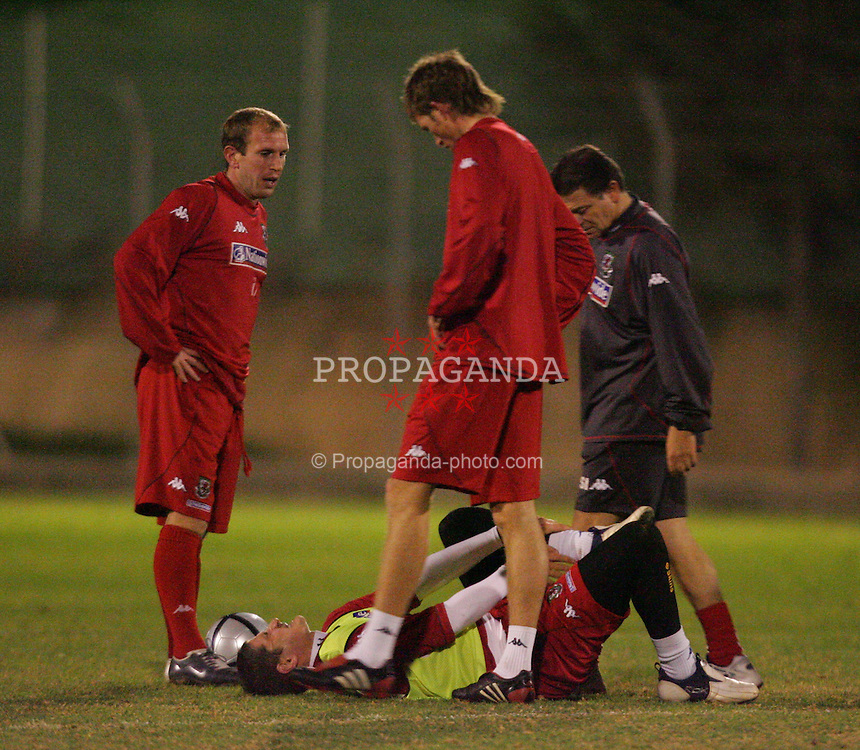LIMASSOL, CYPRUS - MONDAY, NOVEMBER 14th, 2005: Wales' Carl Robinson goes down injured training on a poor pitch in near dark conditions in Gerrmasogia near Limassol ahead of his side's International Friendly match against Cyprus on Wednesday. (Pic by David Rawcliffe/Propaganda)