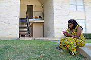 Estella Ndayikunda sits outside her apartment at ParkLane Terrace in Dallas, Texas on October 5, 2014. Ndayikunda lives in the unit directly below Youngor Jallah, who along with her family, have been quarantined and monitored daily for symptoms of Ebola. (Cooper Neill for The New York Times)