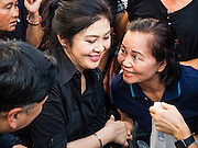 11 NOVEMBER 2016 - BANGKOK, THAILAND: A woman thanks YINGLUCK SHINAWATRA (left) after she bought rice from Yingluck at a rice distribution sale in the Bangkok suburbs. Yingluck Shinawatra, the former Thai Prime Minister deposed in a coup in 2014, has started selling rice directly to Thai consumers. She buys the rice from farmers at market prices and then sells it to urban consumers at the price she paid. She said she's doing it to help out farmers, who are trying to deal with depressed prices. Yingluck is facing prosecution on corruption related charges going back to a rice price support scheme her government used to try to help farmers in 2011 and 2012. Even after the coup, she is still personally popular and hundreds of people showed up to see her at the rice distribution point at a mall in Samut Prakan province, in suburban Bangkok.   PHOTO BY JACK KURTZ