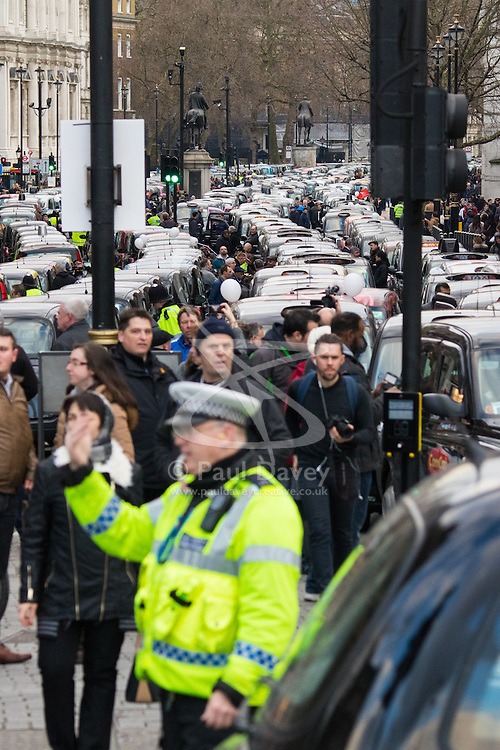 Whitehall, London, February 10th 2016. A policeman directs traffic as an estimated 8,000 cabbies hold a go-slow in protest against what they say is unfair competition from minicab and Uber drivers who do not have to undergo the rigorous training and checks required for the licenced taxi trade. ///FOR LICENCING CONTACT: paul@pauldaveycreative.co.uk TEL:+44 (0) 7966 016 296 or +44 (0) 20 8969 6875. ©2015 Paul R Davey. All rights reserved.