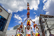 "05 JULY 2014 - BANGKOK, THAILAND: An acrobat team holds toddlers in their human pyramid on a side street in Bangkok during a parade for vassa. Vassa, called ""phansa"" in Thai, marks the beginning of the three months long Buddhist rains retreat when monks and novices stay in the temple for periods of intense meditation. Vassa officially starts July 11 but temples across Bangkok are holding events to mark the holiday all week.    PHOTO BY JACK KURTZ"