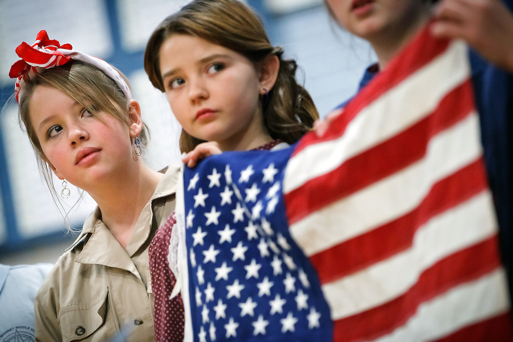 """Elisabeth Arbic, left, dressed as """"Rosie the Riveter"""" and Leeauna Jenkins listen to a poem Tuesday during a Pearl Harbor assembly at Lakes Magnet Middle School."""
