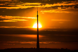 © Licensed to London News Pictures. 06/03/2017. Huddersfield UK. The sun rises this morning behind the UK's tallest freestanding structure, the 1,084 ft Emley Moor transmitting station in Kirklees, West Yorkshire. Photo credit: Andrew McCaren/LNP