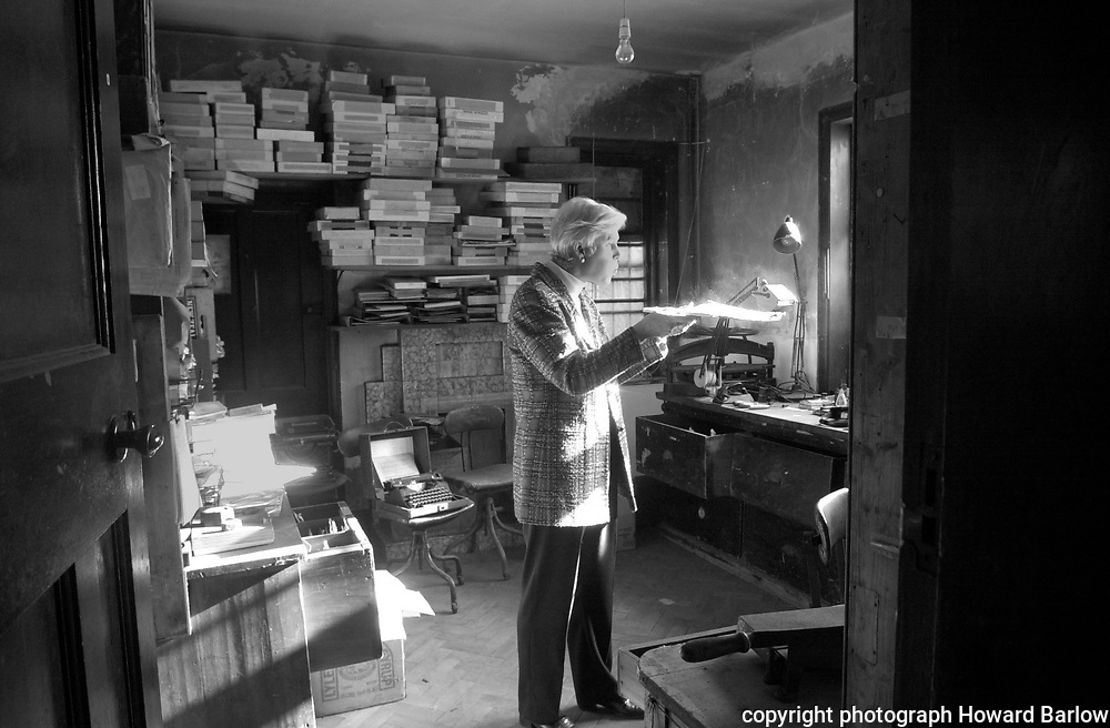 PIC BY HOWARD BARLOW 2000..THE LIVERPOOL HOME OF PHOTOGRAPHER 'EDWARD CHAMBRE HARDMAN' WHO DIED IN 1988 LEAVING 200,000 PHOTOGRAPHS..VIVIENNE TYLER COMPANY SECRETARY OF THE 'EDWARD CHAMBRE HARDMAN TRUST' BLOWING THE DUST OFF WORK IN CHAMBRE HARDMAN'S MOUNTING ROOM.