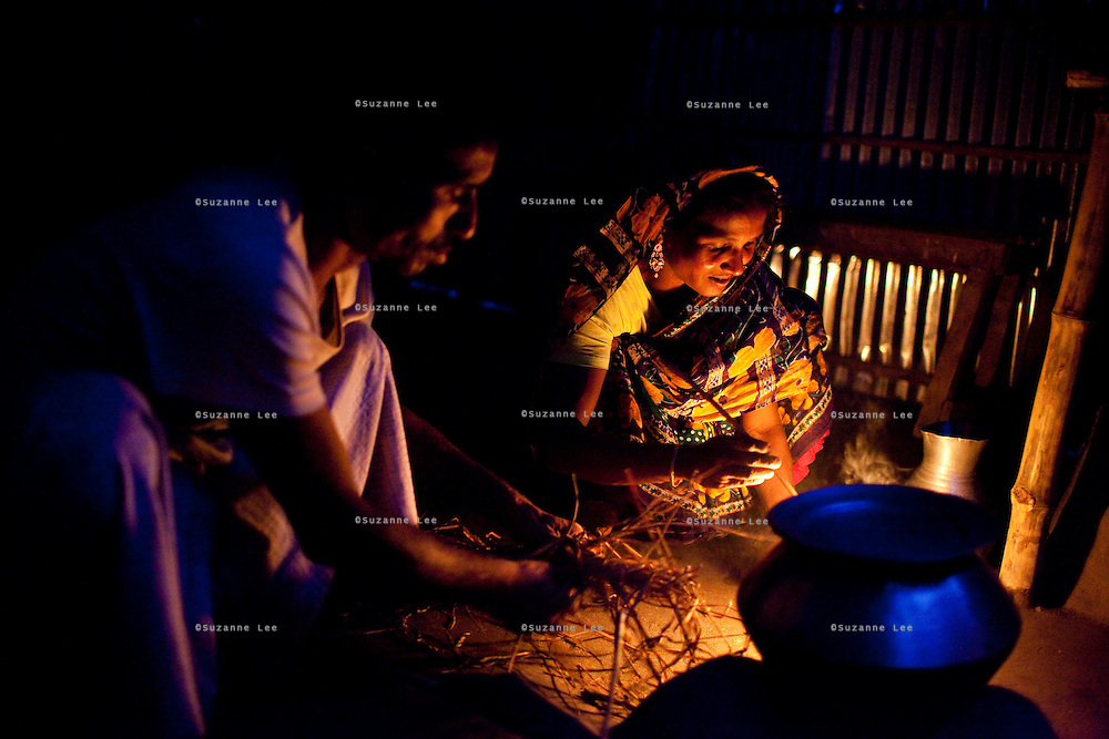 Together with her husband, Mohd. Abu Taleb (41), Shahida Begum, 35, cooks dinner in her home in Palashbari Villlage, Taragonj, Rangpur, Bangladesh on 18th September 2011. She has found financial independence and contributes to the family income by working as a saleswoman, earning 3500 - 5000 Bangladeshi Taka per month. She is one of many rural Bangladeshi women trained by NGO CARE Bangladesh as part of their project on empowering women in this traditionally patriarchal society. Named 'Aparajitas', which means 'women who never accept defeat', these women are trained to sell products in their villages and others around them from door-to-door, bringing global products from brands such as BATA, Unilever and GDFL to the most remote of villages, and bringing social and financial empowerment to themselves.  Photo by Suzanne Lee for The Guardian