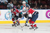 KELOWNA, CANADA - MARCH 23: Colton Heffley #25 of the Kelowna Rockets makes a pass between Rodney Southam #15 and Ty Comrie #11 of the Tri-City Americans on March 23, 2014 at Prospera Place in Kelowna, British Columbia, Canada.   (Photo by Marissa Baecker/Shoot the Breeze)  *** Local Caption *** Colton Heffley; Rodney Southam; Ty Comrie;
