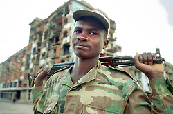 """An Angolan soldier known as """"Bernardo"""" stands in the center of a town in the interior region where fighting between the rebels and government forces left the edifices in ruins. Angola's brutal 26 year-civil has displaced around two million people - about a sixth of the population - and 200 die each day according to United Nations estimates..(Photo by Ami Vitale)"""