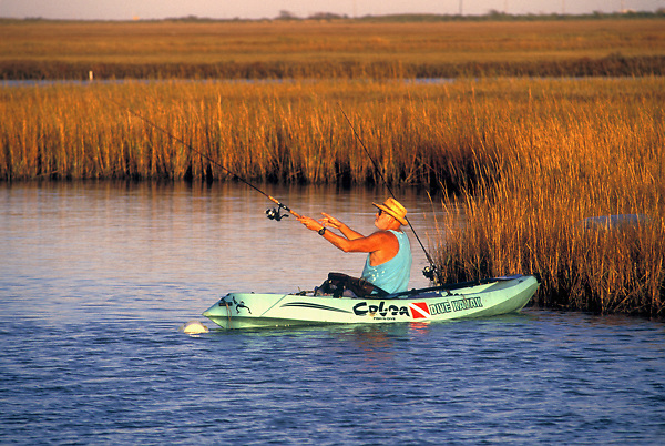 Stock photo of a man casting his rod from his kayak close to shore