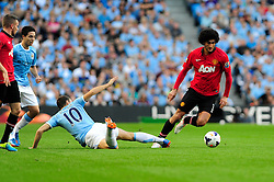 Manchester United's Marouane Fellaini is challenged by Manchester City's Edin Dzeko - Photo mandatory by-line: Dougie Allward/JMP - Tel: Mobile: 07966 386802 22/09/2013 - SPORT - FOOTBALL - City of Manchester Stadium - Manchester - Manchester City V Manchester United - Barclays Premier League