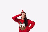 Woman wearing Christmas jumper and party hat against gray background