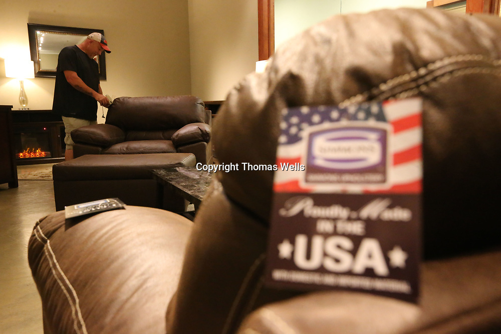 "Stephen Winter attaches ""Made in the USA"" tages to the sofa's and chairs at the United Showroom at the Tupelo Gurniture Market on Wednesday as they get ready for next weeks show."