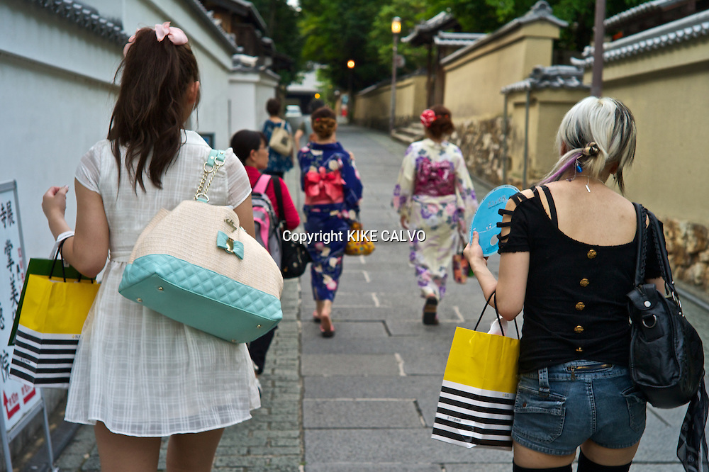 Japanese teens dressed in very modern clothing contrast with others  wearing traditional kimonos near Kiyomizu Temple.