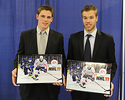 Tyler Seguin (left) of the Plymouth Whalers and Taylor Hall of the Windsor Spitfires with screen shots of themselves in EA Sports NHL 11 at the Canadian Hockey League media conference at the MasterCard Memorial Cup in Brandon, MB on Friday. Photo by Aaron Bell/CHL Images