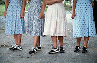 1984, Lancaster County, Pennsylvania, USA --- Viewed from the waist down, Mennonite women wear floral print dresses and matching black tennis shoes. --- © Owen Franken