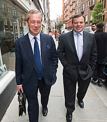 © Licensed to London News Pictures. 15/05/2015.  NIGEL FARAGE leaving UKIP party headquarters with UKIP donor AARON BANKS (right) in Mayfair, London on May 15, 2015. Farage has been critiqued by members of the UKIP party after a u-turn on his decision to stand down as leader. Photo credit: Ben Cawthra/LNP
