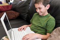 6 year boy hapy playing with computer at home