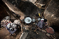 A elderly woman prepared food for here family while her sick husbend holds their grandchild in a cave in the Nuba mountains at the begining of the war. Thousands of people have fled to caves to live after repeated bombing attacked by Sudan government forces on civilians areas.