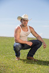 sexy cowboy squatting in a field