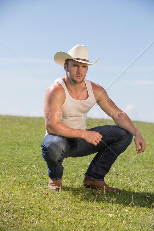 sexy cowboy squatting in a field