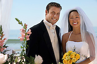 Bride and Groom with flowers at ocean (portrait)