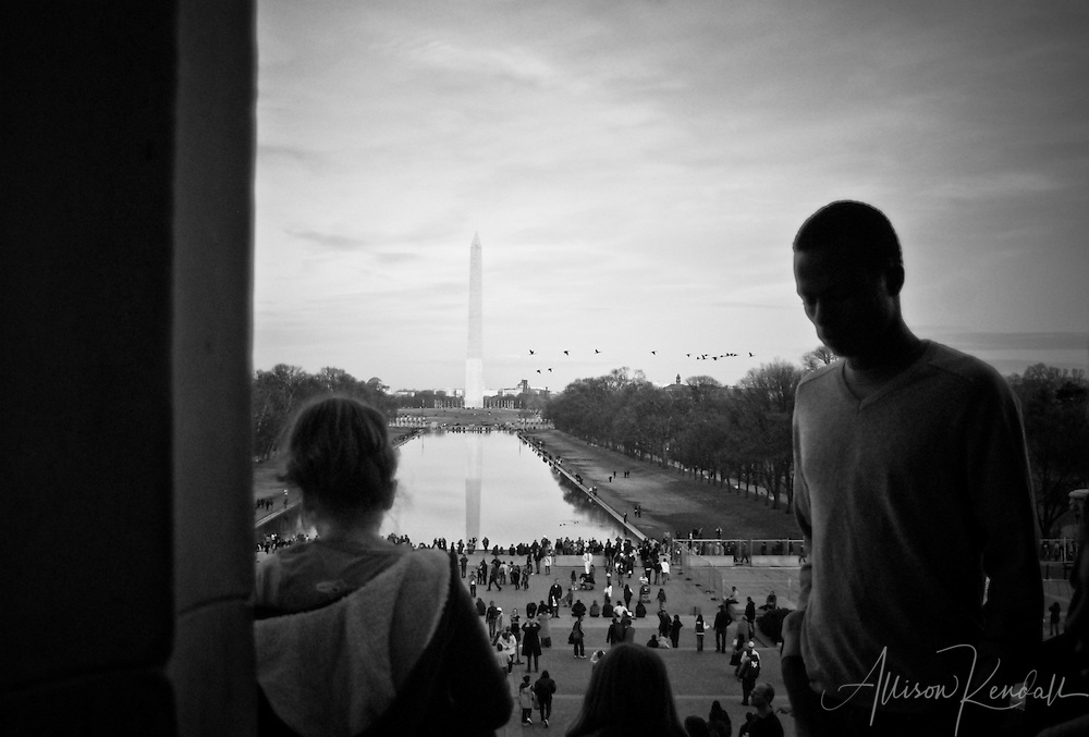 People crowd the steps of the Lincoln memorial with the Washington Monument reflecting in the distance.