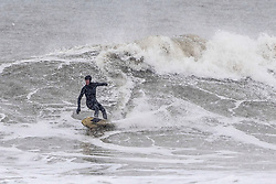 © Licensed to London News Pictures. 01/03/201. Falmouth, UK. A hardy surfer braves the snow blizzard to go surfing in the freezing sea at Falmouth in Cornwall as the UK is hit by storm Emma. .  Photo credit: Mark Hemsworth/LNP
