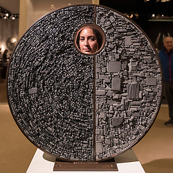 "© Licensed to London News Pictures. 29/06/2016. London, UK.  A staff member looks through ""Paradox"" by Tom Stogdon, a stainless steel disc covered in hot bronze cut slate, at the preview, in Chelsea, of Masterpiece London, the leading international fair for art and design from antiquity to the present day with works from 154 world-renowned exhibitors on sale.  The fair is open until 6 July.Photo credit : Stephen Chung/LNP"