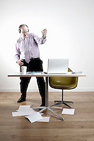 Businessman with earphones fooling around at desk
