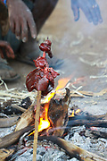 Hunted animal meat is being cooked on an open fire at a Hadzabe village. Photographed at Lake Eyasi, Tanzania