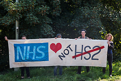 West Hyde, UK. 14th September, 2020. Environmental activists from HS2 Rebellion stand holding a NHS Not HS2 banner close to the South Portal site for the HS2 high-speed rail link. Anti-HS2 activists blocked two gates to the same site for the controversial £106bn rail link, one remaining closed for over six hours and another for over twelve hours.