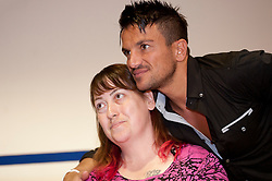 """Peter Andre poses fo photos with a fan after showing her a tatoo during a  book signing event for  his new childrens books """"The Happy Birthday Party"""" and """"A New Day at School"""" in WH Smiths Sheffield on 6th September 2011 .Image © Paul David Drabble"""