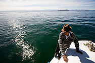 A boatman on Lake Titicaca raises the anchor before departing on a tour on Lake Titicaca, Bolivia.