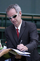 Former Wimbledon Champion , now commentator John McEnroe signs autographes on Centre Court. Wimbledon Tennis Championship, Day 6, 28/06/2003. Credit: Colorsport / Matthew Impey DIGITAL FILE ONLY