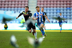 Michael Jacobs of Wigan Athletic and Harrison McGahey of Rochdale chase down the ball as Pigeons fly up off the pitch at The DW Stadium - Mandatory by-line: Robbie Stephenson/JMP - 24/02/2018 - FOOTBALL - DW Stadium - Wigan, England - Wigan Athletic v Rochdale - Sky Bet League One