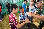 "11 JANUARY 2014 - BANGKOK, THAILAND:  A Thai soldier shows boys a TAVOR Assault Rifle during Children's Day in Bangkok. The Royal Thai Army hosted a ""Children's Day"" event at the 2nd Cavalry King's Guard Division base in Bangkok. Children had an opportunity to look at military weapons, climb around on tanks, artillery pieces and helicopters and look at battlefield medical facilities. The Children's Day fair comes amidst political strife and concerns of a possible coup in Thailand. Earlier in the week, the Thai army announced that movements of armored vehicles through Bangkok were not in preparation of a coup, but were moving equipment into position for Children's Day.     PHOTO BY JACK KURTZ"