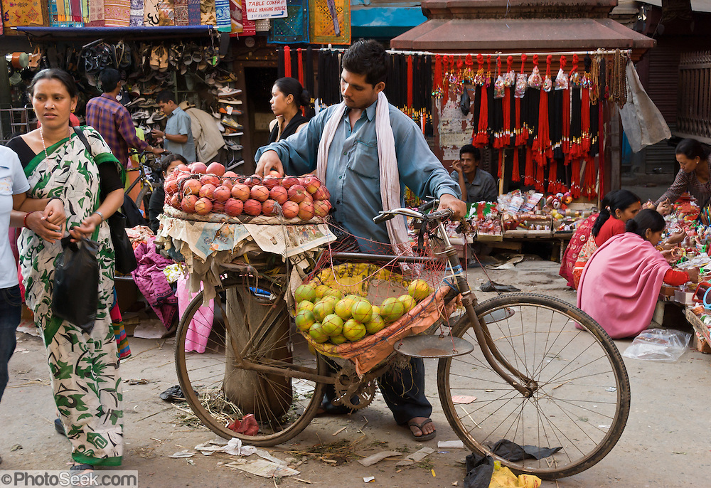 "A vender sells fruit from a bicycle in Kathmandu, Nepal. Kathmandu, the largest city in Nepal (700,000 people), is sometimes called ""Kantipur"". The city stands at an elevation of 6235 feet / 2230 meters."