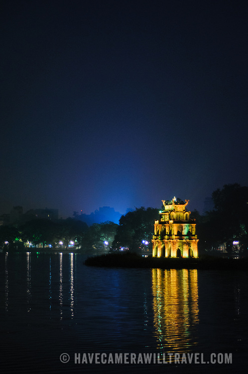 Night photo of the lights of Turtle Tower (also known as Tortoise Tower on a small island in Hoan Kiem Lake in the historical center of Hanoi, Vietnam. City lights in the background light up a deep blue sky. Copyspace at top of frame.