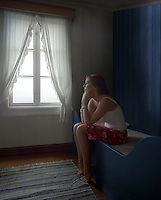 Sad Woman Sitting Alone in Room daydreaming side view