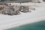 Coastal buildings lie in ruins behind a sand fence.  Cleanup of destruction is still going on three years after Hurricane Ivan hit in 2005.
