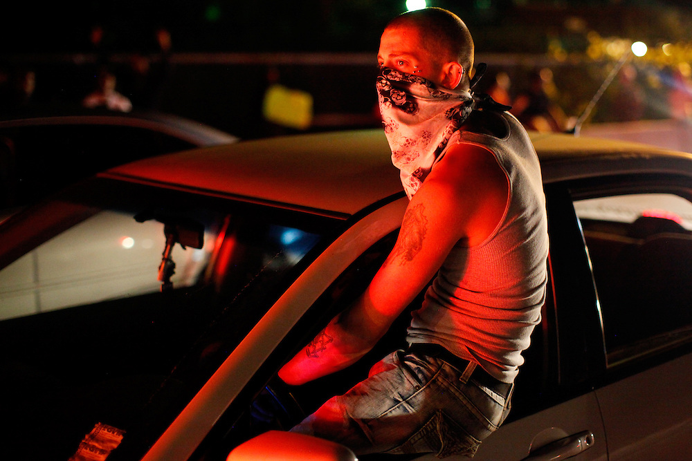A demonstrator drives his car while sitting outside the window. Protestors piled into their cars and cruised up and down West Florissant Avenue, honking there horns and blaring music well into the night. Protests have been ongoing in Ferguson, Missouri since the shooting death of Michael Brown, the eighteen-year-old unarmed teen killed by police on August 9, 2014.